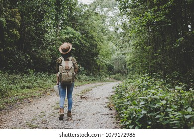 traveller women walking on road in the forest