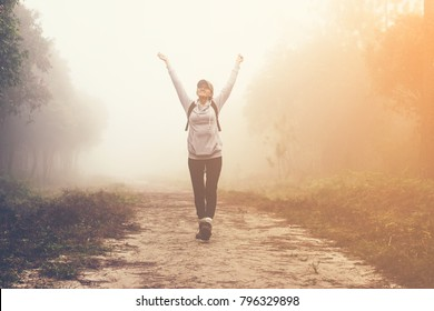 traveller women walking on road in the forest paths in the woods and foggy, hiker women enjoying the beautiful nature with fog.