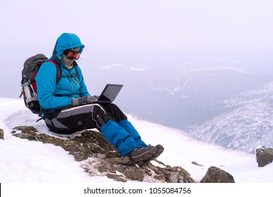 traveller working with a laptop in winter on top of a mountain during the snowstorm