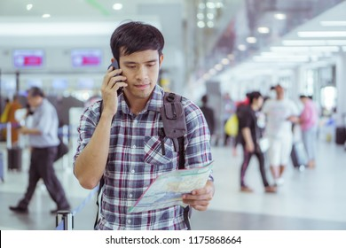 traveller with world map in hand and using mobile phone in the airport background. Handsome caucasian man,  tourism, or holiday vacation travel concept.