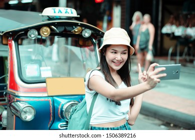 Traveller young Asian backpack woman wearing hat taking a picture by mobile phone with traditional Thai Tuk Tuk Taxi at Khao San road and , famous travelling landmark in Bangkok city of Thailand.