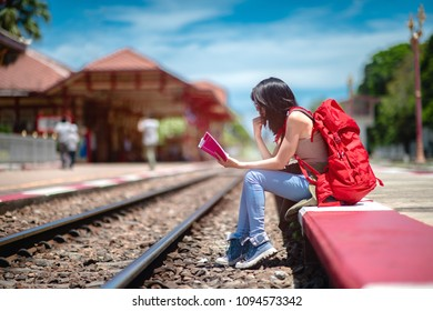 traveller young woman sitiing nearby railway station waiting incoming train arrive to the station, reading a book keep waiting time consumption, tourist and traveling in vacation and holiday