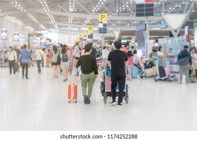 Travellers carries luggage and trolley at the airport terminal.