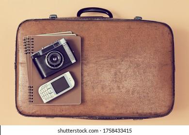 Arrière-plan voyage. Voyageur prêt. Bloguer en voyage. Vue de dessus de valise, appareil photo et téléphone portable. Sacoche à bagages vintage