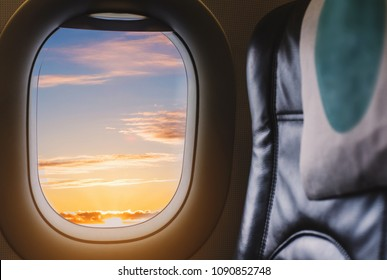 Travelling by air plane, looking through plane window enjoying beautiful sunrise from aerial view