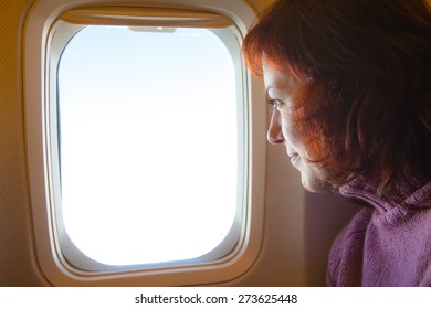 Travelling by air - woman is sitting in the airplane looking  through window