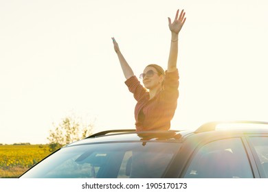 Travelling by car. The girl looks out of the car hatch.  young woman sitting  on the car roof  and enjoying the life