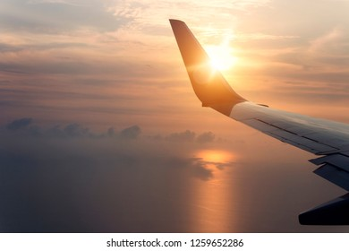 Travelling concept; flying and traveling, view from airplane window on the wing on sunset time. Morning sunrise with Wing of an airplane. Photo applied to tourism operators.