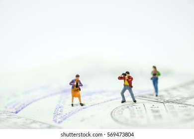 Travelling concepts.  Group of miniature mini figures with camera taking photo and standing on passport with stamps