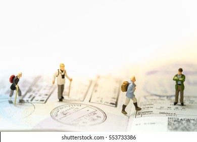 Travelling concepts. Group of traveler miniature people mini figures with backpack stand and walking on passport with immigration stamps