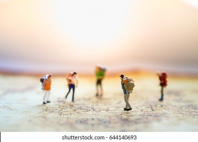 Travelling concepts. Group of traveler miniature mini figures with backpack standing and walking on world map