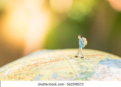 Travelling concepts. Traveler miniature mini figures with backpack stand and walking on globe world map balloon