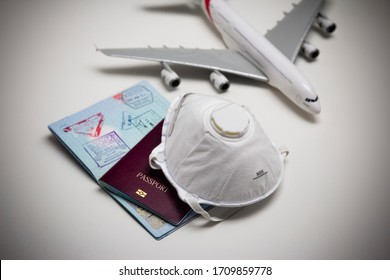 Travelling during corona virus epidemic. Passport and protective face mask respirator. Coronavirus and travel concept. Travelling with face mask. Corona virus prevention. Flights cancelled. Stay Home.