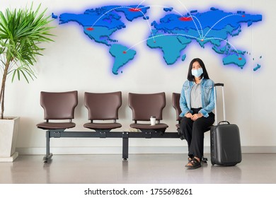 Travelling during corona virus epidemic. Asian woman wearing face mask to protect virus with luggage and empty chairs in the departure hall at airport and Epidemic on the world map.
