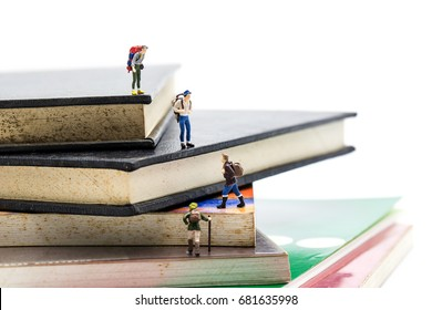 Travelling and Education concepts. Group of miniature people mini figures with backpack   walking and climbing on a mountain of textbooks
