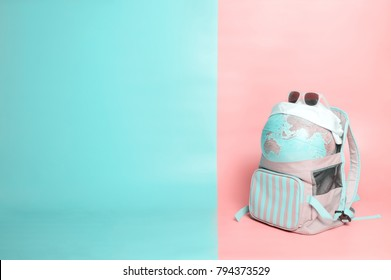 Travelling globe going on vacation in backpack with sunglasses and  bandana on soft pink and light mint pastel colored background, space for text