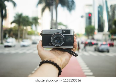 Travelling guy holding a vintage camera with the blurred city in the background