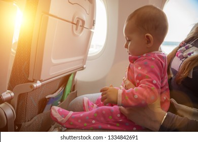 Travelling with infant. Mother and baby sitting together in airplane near the window in sunny day