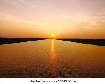 The travelling and life concept. The sun is falling in the dusk. The golden light of the sun reflects on the water surface with many small wave of the river. Selective focus and copy space.