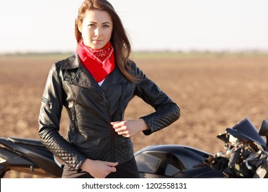 Travelling on bike. Serious beeautiful cool motorcyclist zips black leather jacket, has red bandana on neck, enjoys long route on motobike, poses outdoor against nature background, stops on road