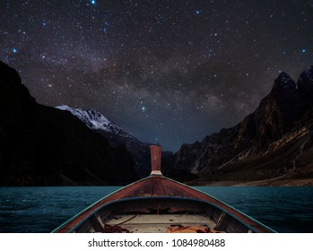 Travelling on lake at night by boat, sky full of star and milky way with mountains valley