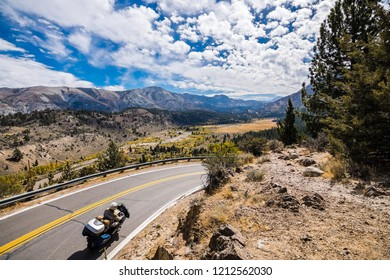 Travelling on a motorcycle towards Sonora Pass; beautiful alpine valley and mountain ridges visible in the background; Eastern Sierra mountains, California
