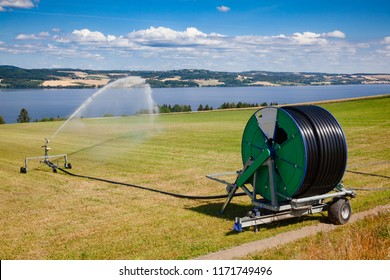 Travelling sprinkler with hose reel irrigation machine   spaying water over a farmland during a drought summer