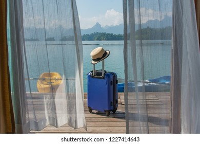 Travelling suitcase on the floor with lake , canoe and mountain background, door curtain in foreground.