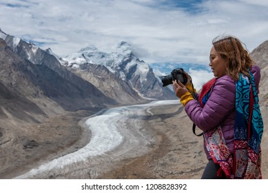 Travelling woman with camera on rang of mountains with snow, India.