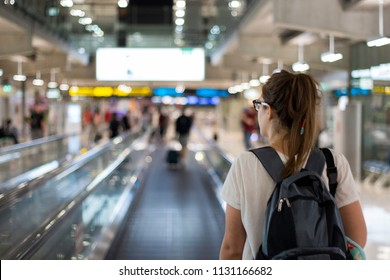 A travelling woman walking on the airport with her backpack through the duty free zone.