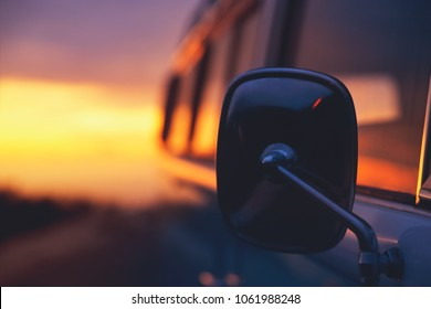 Travels in camper van, closeup photo of side view mirror over sunset background, adventurous journey in the house on the wheels, freedom and recreation concept
