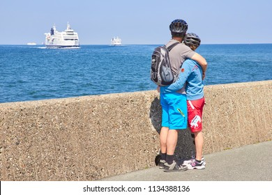 TRAVEMUNDE, GERMANY - JUNE 11, 2013: Back view of couple on embankment