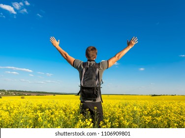 Traverl concept. Man hands up in yellow field over blue sky