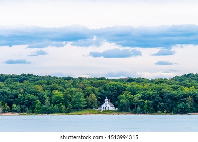 Traverse City, Michigan / USA - August 31 2019:  People walk on the beach in front of the Old Mission Point Lighthouse on Old Mission Peninsula near Traverse City, Michigan, as viewed from the water.