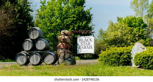 Traverse City, Michigan / USA - June 04 2019:  Black Star Farms Winery Vineyard sign with stack of barrels, Old Mission Peninsula, Traverse City, Michigan, USA.