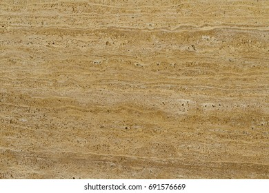 Travertine Gold. Pattern of natural origin on the surface of the stone, close-up. Travertine rich golden-yellow hue. An amazing combination of organic and bright colors.