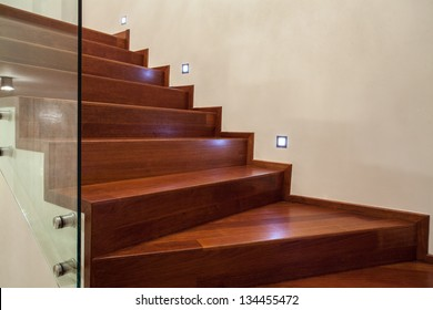 Travertine house- Horizontal view of brown, wooden stairs in luxury interior