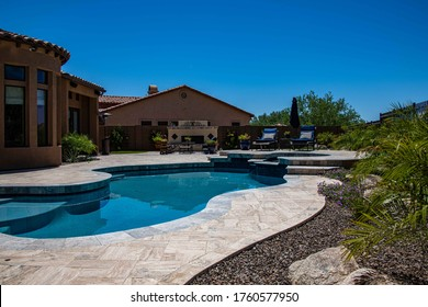 A travertine patio with a pebble tech pool in a desert landscaped backyard.