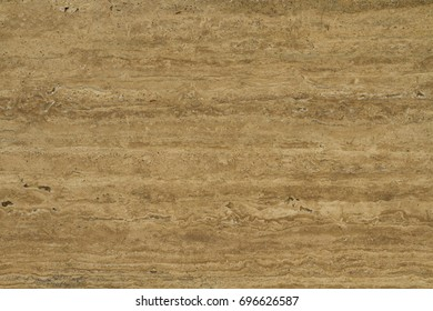 Travertine. Pattern of natural origin on the surface of the stone, close-up. Travertine rich golden-yellow hue. An amazing combination of organic and bright colors.