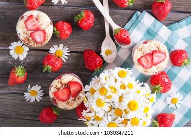 trawberry tiramisu, trifle, custard dessert in a glass with fresh strawberry ,chamomile on a wooden background