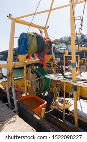 Trawl nets wound up on net drums a wide powered spool on the stern of a commercial fishing vessel in Mevagissey harbour in Cornwall England