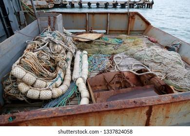 Trawl, pelagic boards, fishing net lies on the fishery deck of a small fishing seiner