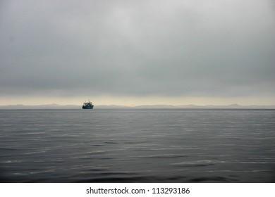 Trawler in misty seascape, Walvis Bay, Namibia