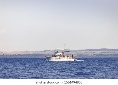 A trawler sailing in the waters in front of the Tuscan coast