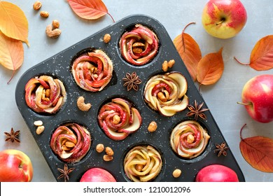 Tray of apple roses baked in puff pastry on gray concrete background with Autumn leaves and red apples