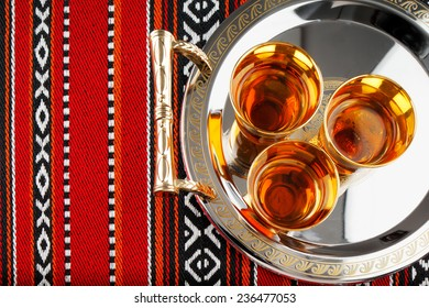 A tray of Arabian tea cups is placed on Arabian woven fabric. Tea symbolise Arabian hospitality
