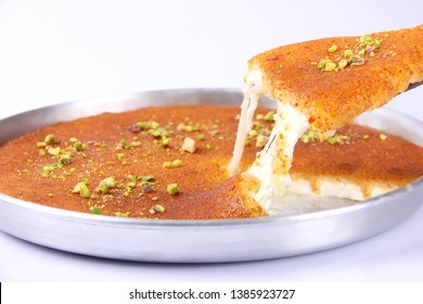 A tray of Baked Kunafa, a piece been sliced off and showing gooey cheese. On a white background.