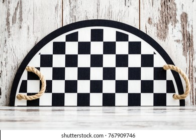 Tray with black and white checkers pattern and handles on white wooden background