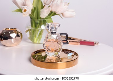 Tray with bottle of perfume on table