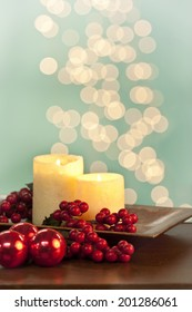 Tray of candles and red berries with red ornaments with lights in the background. Shot with copy space.